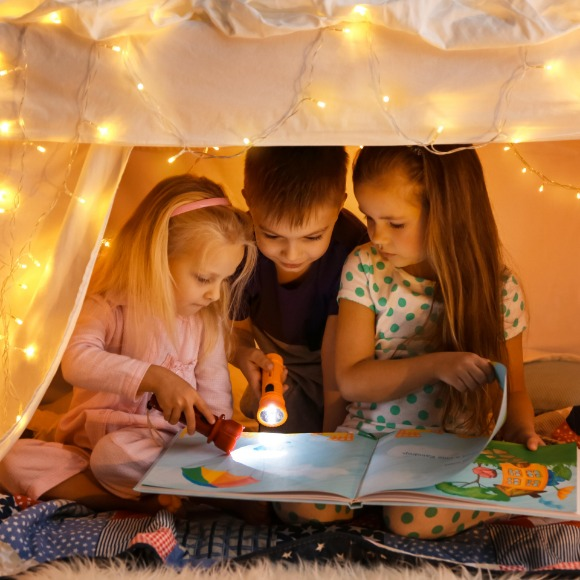 kids reading a book inside a tent