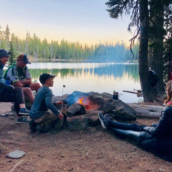 boy roasting marshmallow at campfire with family