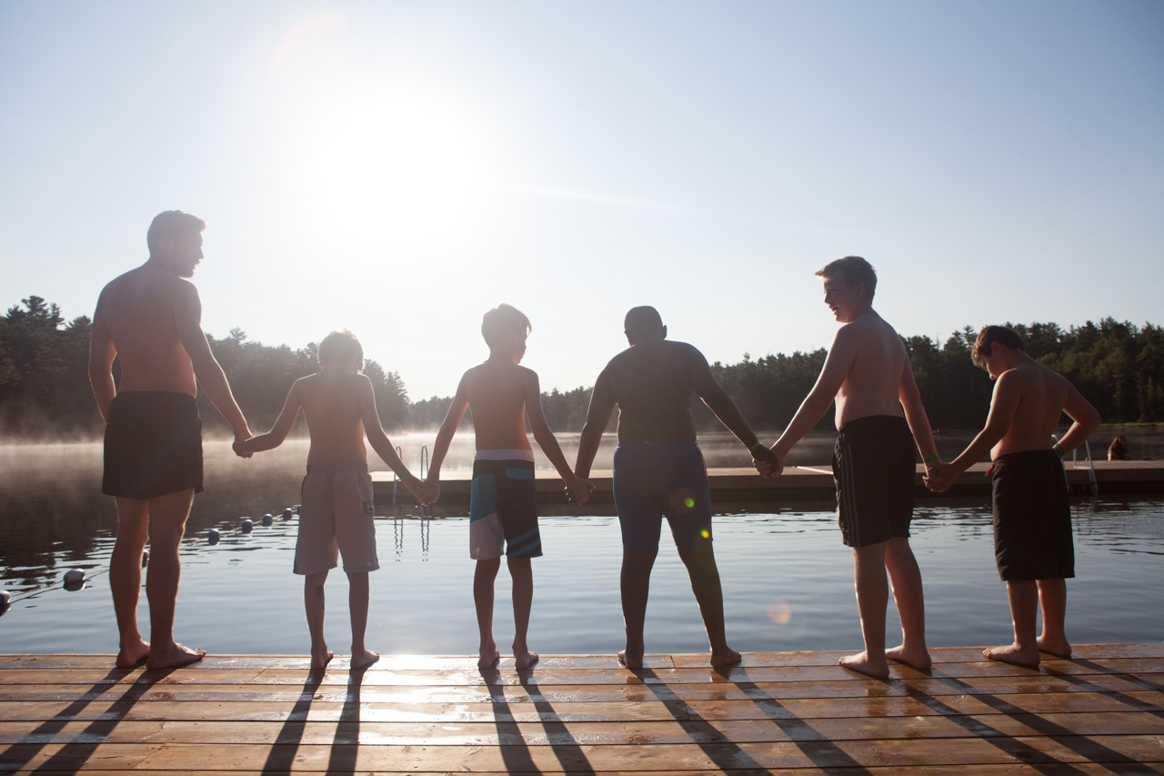 boys standing on dock in a straight line holding hands facing water
