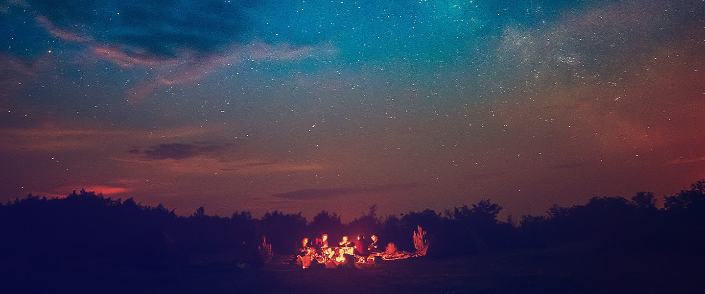 people sitting around campfire at night, surrounded by stars