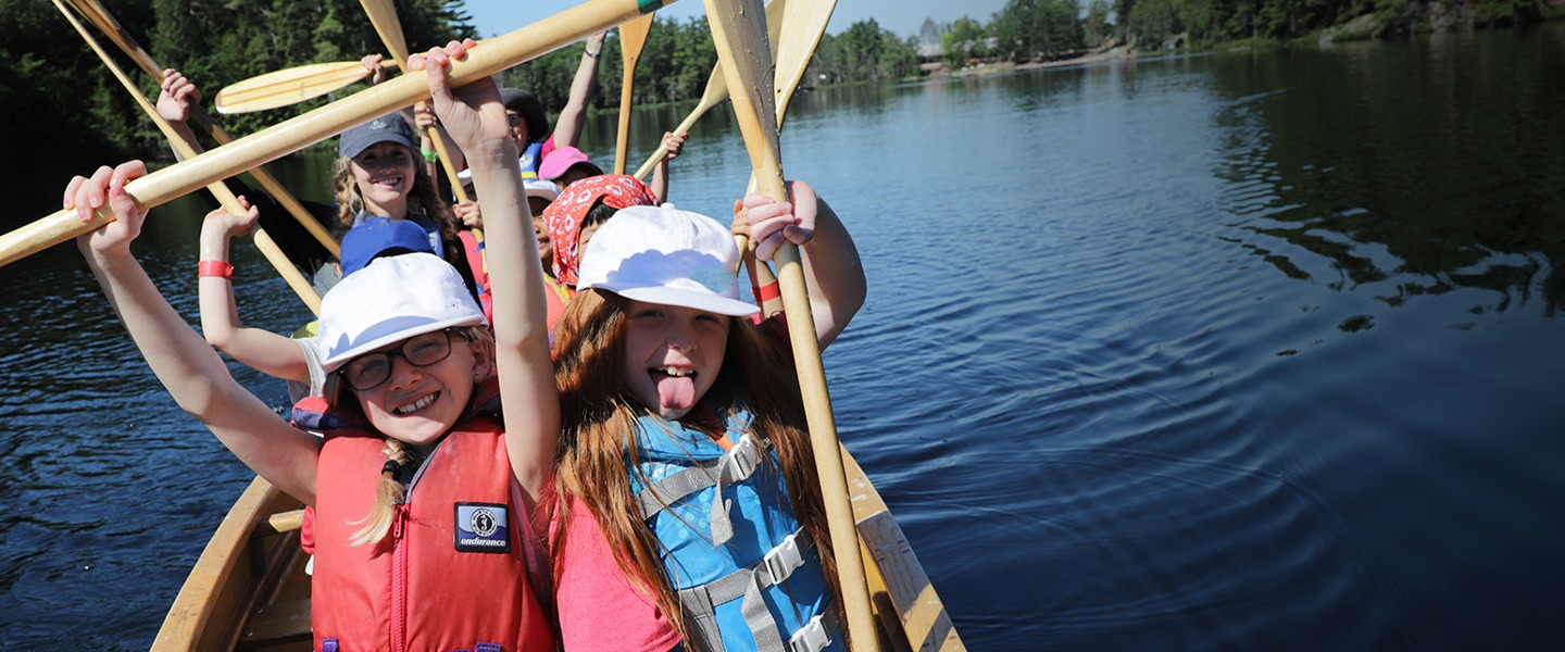 group of kids holding up paddles in a canoe on a lake
